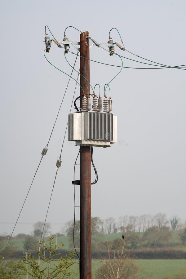 Tr?elektricitetspol med tr?dar, isolatorer och transformatorn arkivbilder