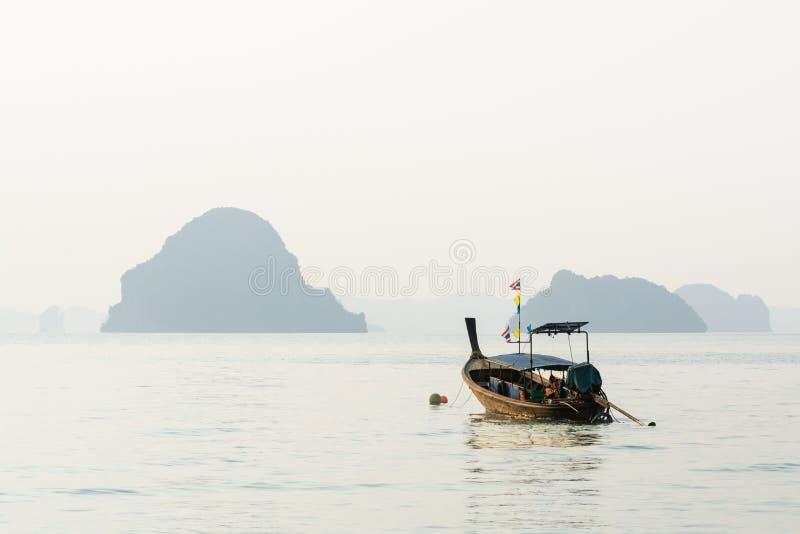 Tr?fartyg f?r l?ng svans som f?rt?jas p? den Klong Muang stranden p? solnedg?ngen i det Krabi landskapet, Thailand arkivfoto