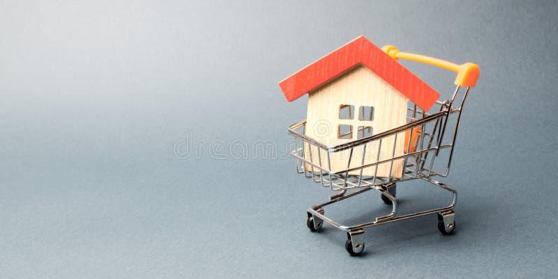 Tr?hus i en supermarketsp?rvagn Begreppet av att k?pa ett hus eller en l?genhet som man har r?d med hus L?nande och billiga l?n arkivfoton