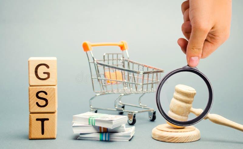 Tr?kvarter med ordet GST, pengar och en supermarketsp?rvagn med en domares auktionsklubba Skatt, som l?ggs p? p? f?rs?ljningen av royaltyfri bild