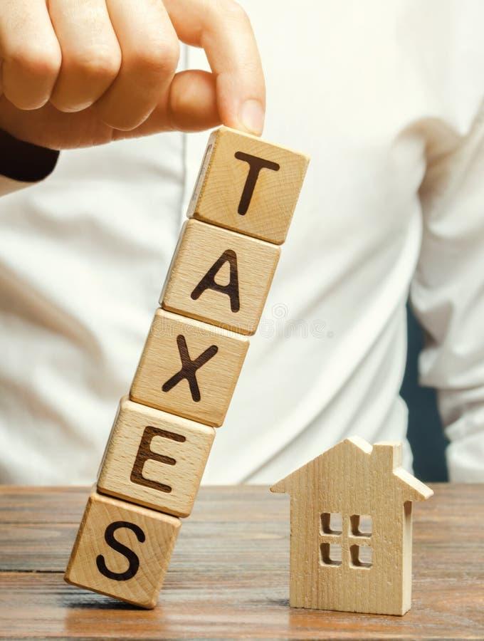 Tr?kvarter med ordskatterna faller p? ett miniatyrhus Begreppet av skattb?rdan p? hus, l?genhet, egenskap arkivbild