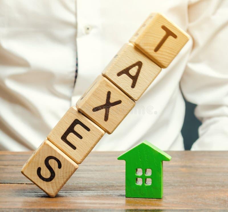 Tr?kvarter med ordskatterna faller p? ett miniatyrhus Begreppet av skattb?rdan p? hus, l?genhet, egenskap royaltyfria foton