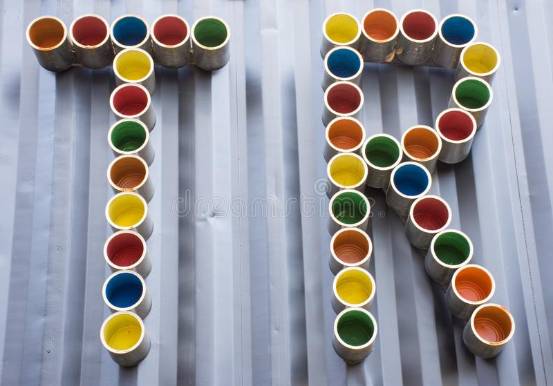 TR letters like abbreviation made by colorful tin cans are on dark wall as background. Using combination of letters as the abbrevi. Ated TR Turkey as country or stock photo