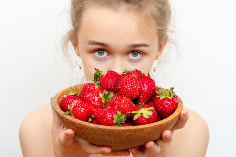 Tr?platta med jordgubbar i flickahand p? ljus bakgrund royaltyfri foto