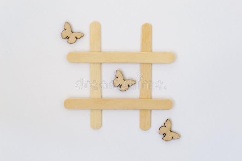 Tr?s borboletas de madeira encontram-se em seguido no jogo do tique-TAC-dedo do p?, em uma grade em um fundo branco ver?o do conc imagem de stock