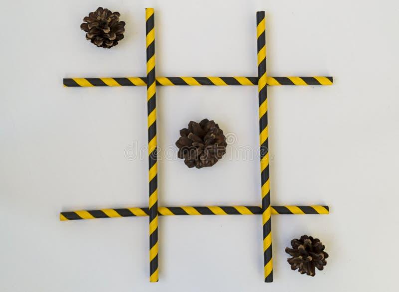 Tr?s cones de abeto marrons encontram-se em seguido em um jogo do tique-TAC-dedo do p?, em uma grade em um fundo branco A grade c fotografia de stock