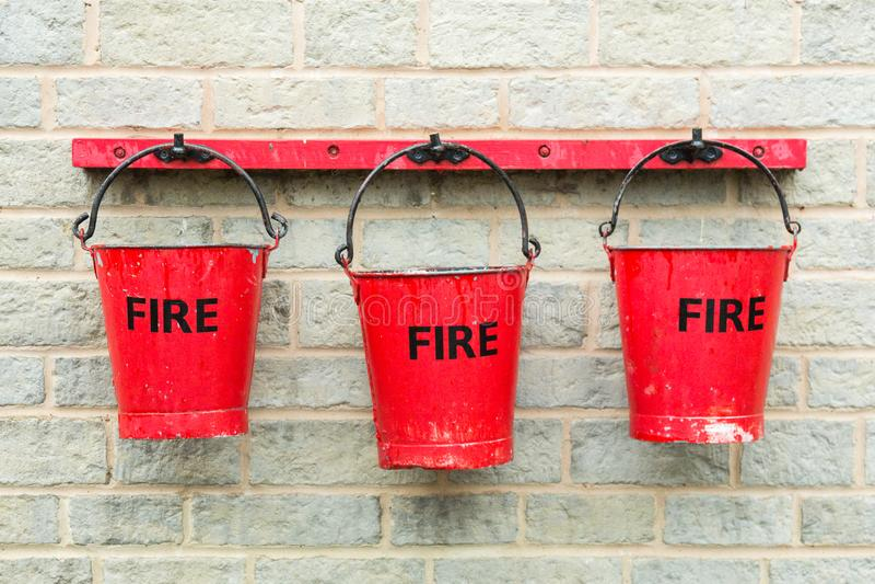 Tr?s cubetas de fogo que penduram em uma parede fotografia de stock royalty free