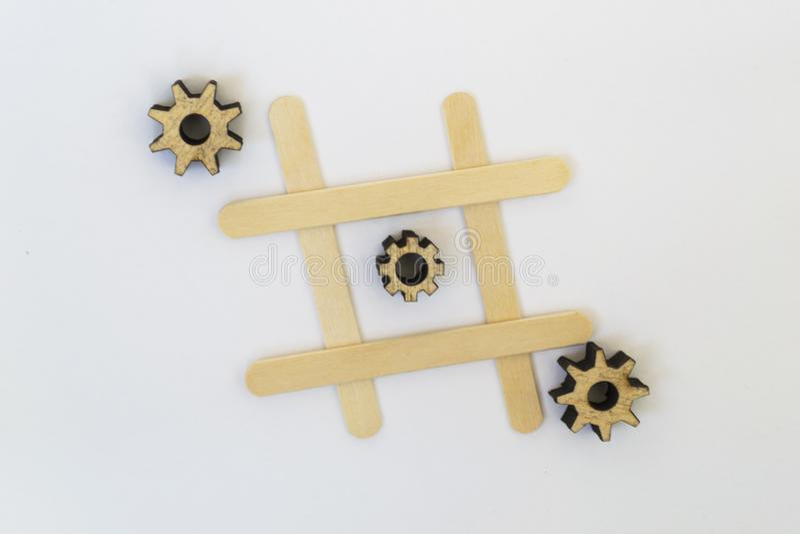 Tr?s engrenagens de madeira da mentira do mecanismo em seguido em uma linha no jogo do dedo do p? do tac do tique, em uma grade e fotos de stock