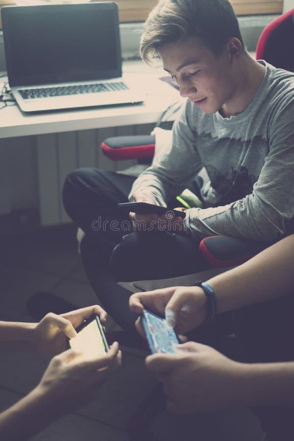 Tr?s homens caucasianos novos do adolescente jogam tudo junto com o dispositivo do telefone celular aos jogos de v?deo como o cl? fotografia de stock royalty free