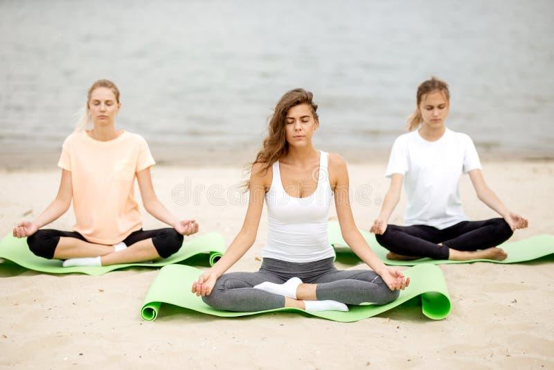 Tr?s mo?as magros sentam-se em uma ioga levantam com os olhos de fechamento em esteiras no Sandy Beach ao lado do rio em um dia m fotografia de stock royalty free