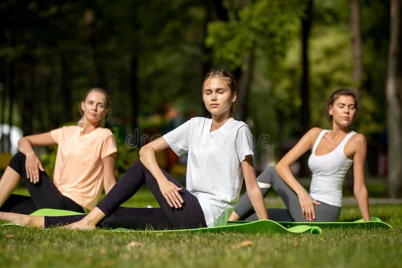 Tr?s mo?as que fazem o estic?o em esteiras da ioga na grama verde no parque no ar livre fotografia de stock royalty free