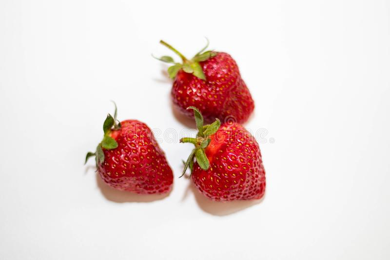 Tr?s morangos vermelhas com caudas verdes encontram-se em um fundo branco, em torno da sombra macia fotografia de stock