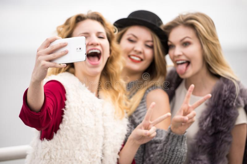 Tr?s mulheres que tomam o selfie exterior imagem de stock