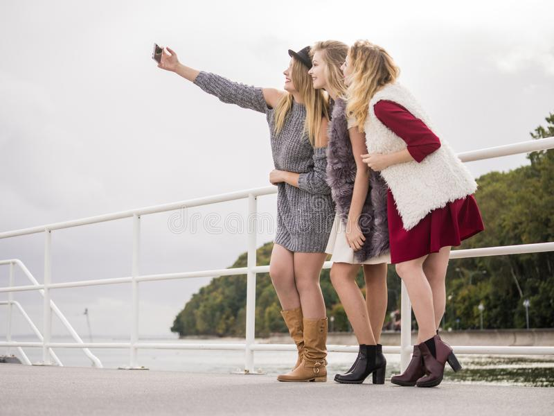 Tr?s mulheres que tomam o selfie exterior imagens de stock royalty free