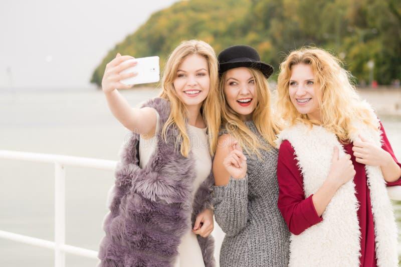 Tr?s mulheres que tomam o selfie exterior fotos de stock