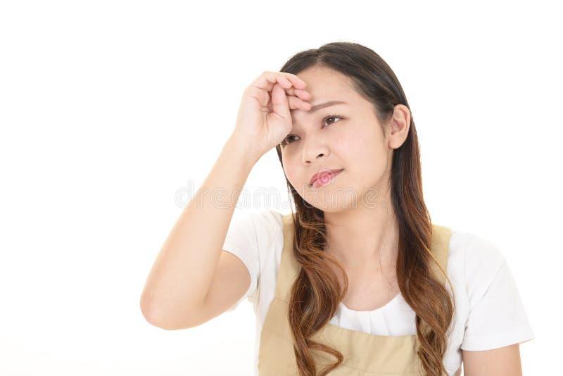 Tr?tt asiatisk hemmafru fotografering för bildbyråer