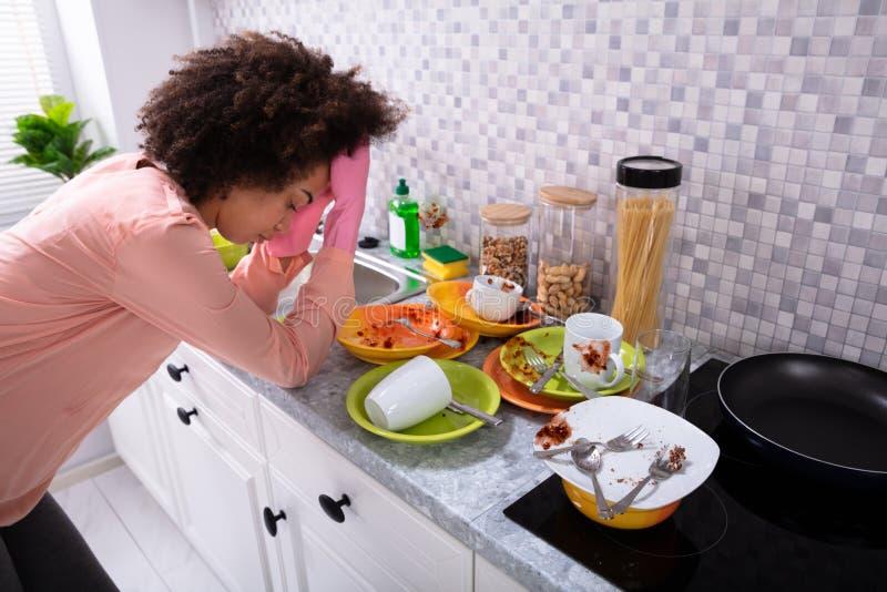 Tr?tt kvinna som lutar n?ra vask med smutsiga redskap royaltyfria bilder