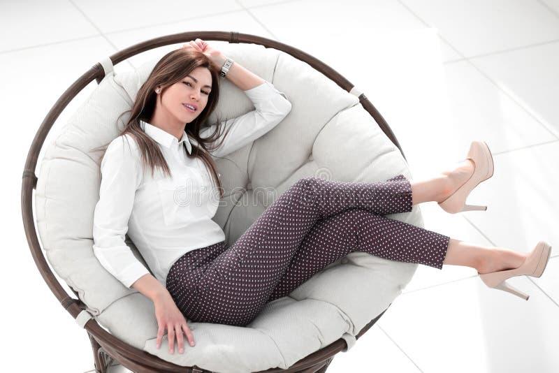 Tr?tt ung kvinna som vilar i en mjuk rund stol fotografering för bildbyråer