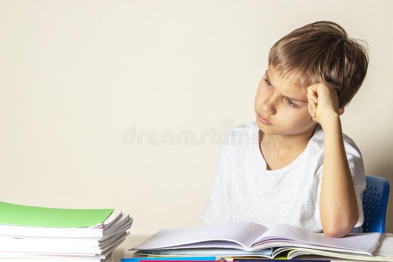 Tr?tt uppriven skolpojke med h?gen av skolb?cker och anteckningsb?cker arkivfoto