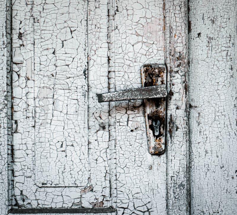 Tração de madeira fechado velha com um puxador da porta oxidado do ferro O fundo não é nenhuma pintura livre imagens de stock royalty free