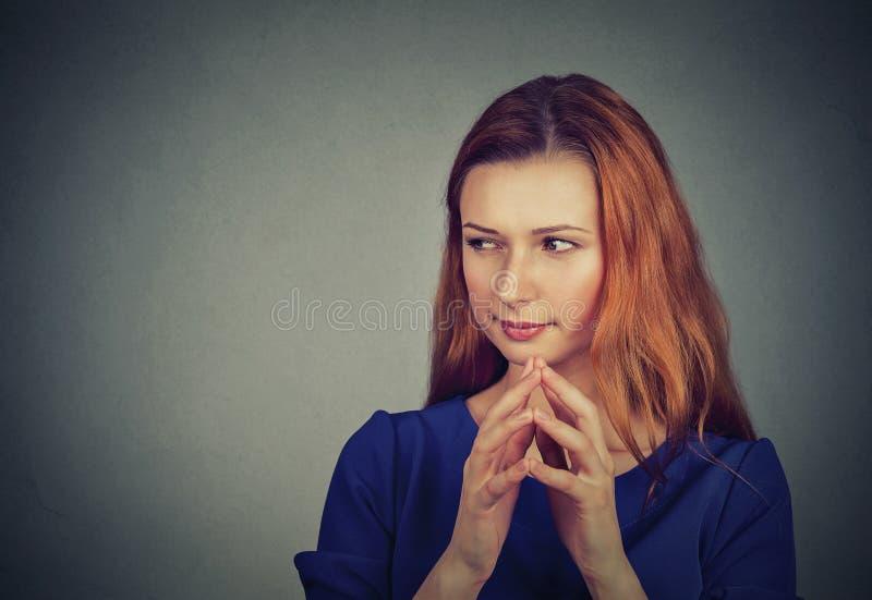 Traçage sournoise, astucieuse, intrigante de jeune femme quelque chose images libres de droits