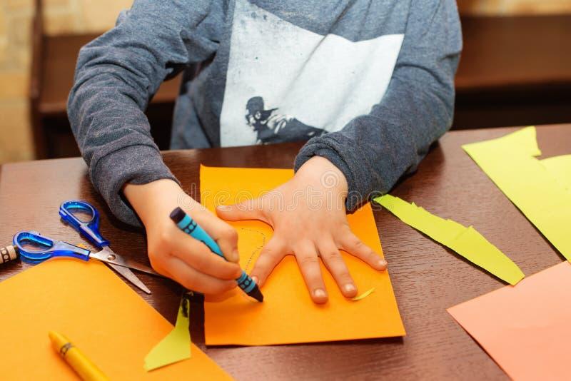 Traço da criança em torno de uma mão no papel com pastéis foto de stock