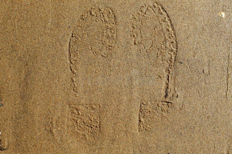 Traços de sapatas humanas na areia do banco de rio da cidade foto de stock royalty free
