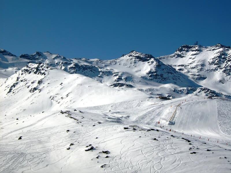 Traços do esqui e inclinação do esqui nas montanhas imagem de stock royalty free