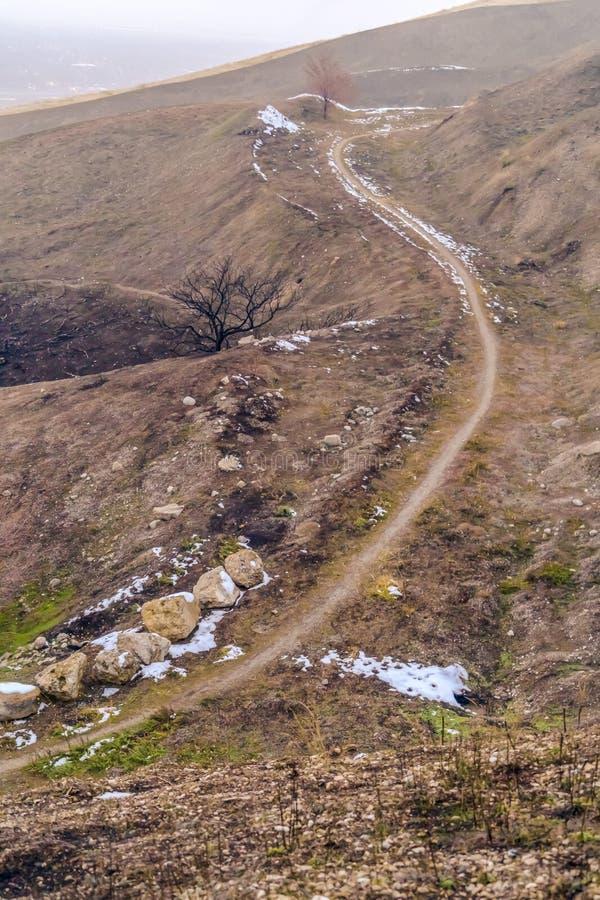 Traînée étroite sur le terrain brun sec d'une colline rocheuse contre le ciel flou image stock