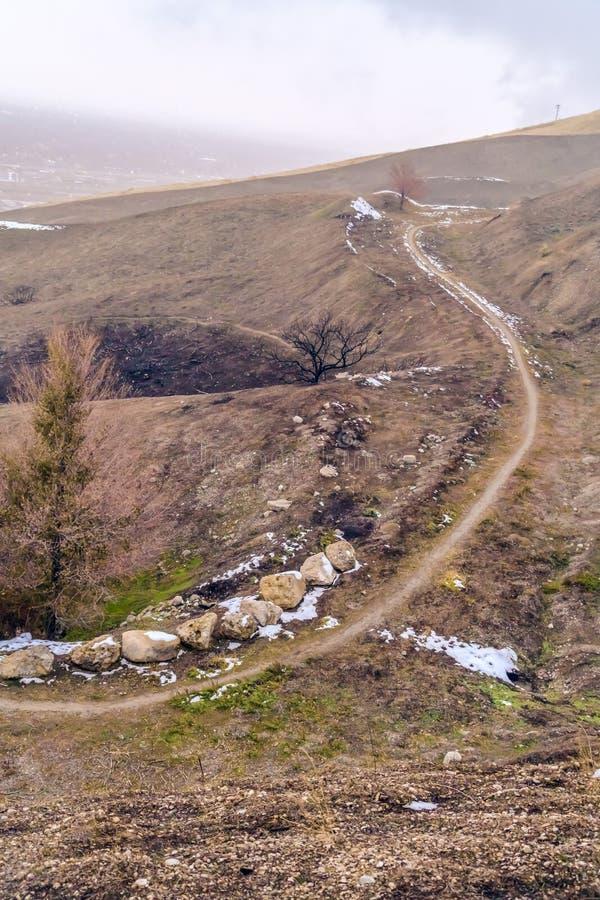 Traînée étroite sur une colline brune avec le ciel flou à l'arrière-plan images libres de droits