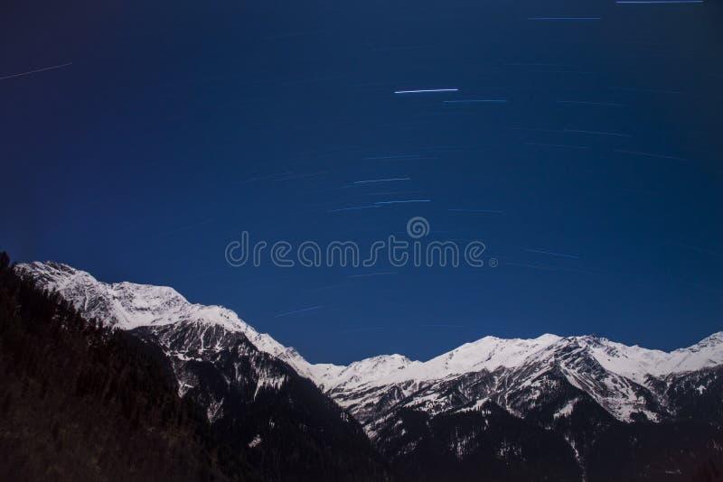 Traînée d'étoile au-dessus de montagne de neige photos stock
