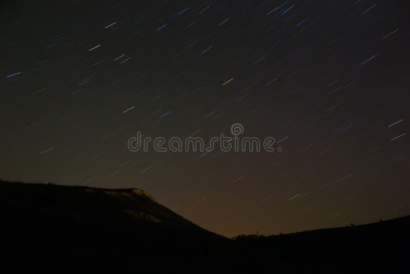 Traînée d'étoile dans le ciel nocturne La pente de la montagne sur un dos photos stock