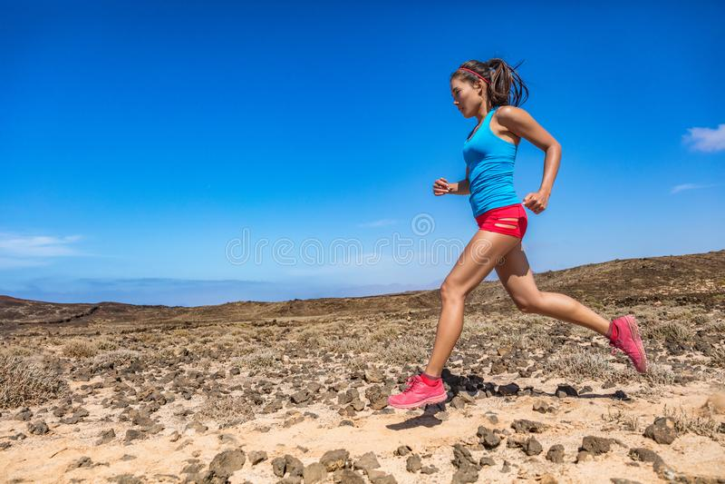 Traînée d'athlète de femme d'ajustement fonctionnant dans le désert extérieur Vue de côté d'extérieur pulsant de coureur asiatiqu images stock