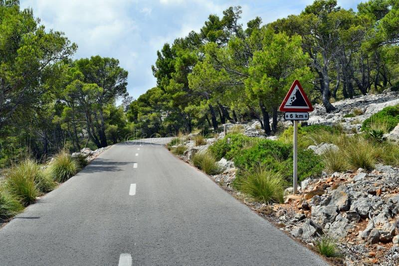 Traînée dangereuse avec le panneau routier à la manière au phare de Formentor en Majorque photos stock