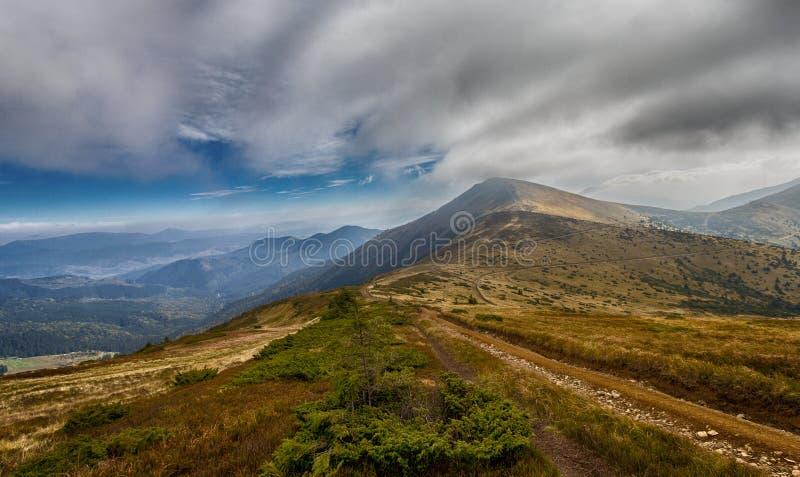 Traînée dans les montagnes sous le ciel nuageux image stock