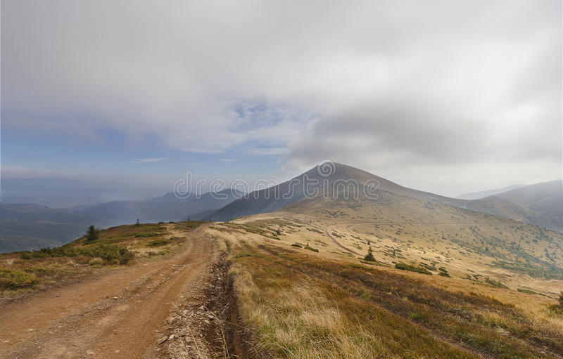 Traînée dans les montagnes sous le ciel nuageux photo libre de droits
