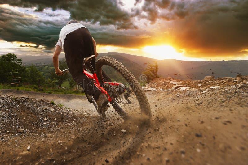 Traînée de coucher du soleil de Mountainbiker en descendant image libre de droits