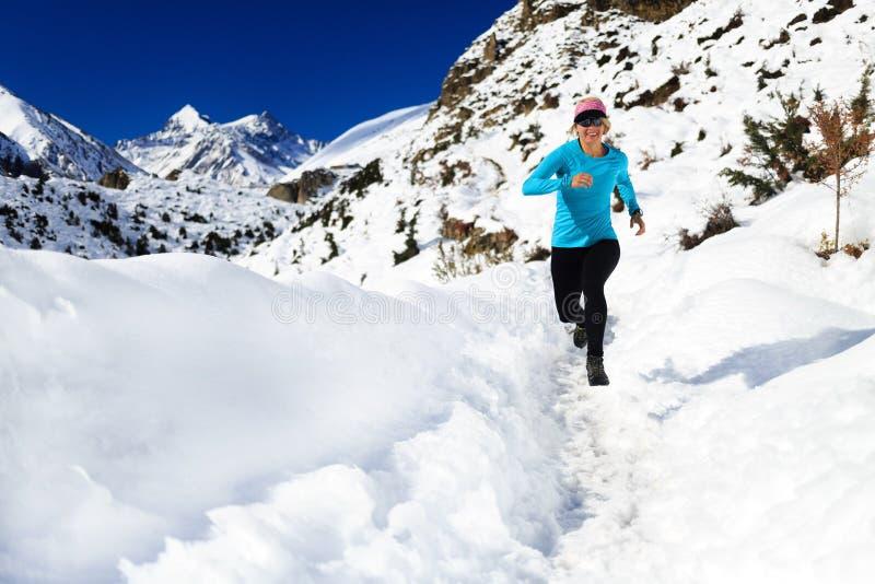 Traînée de femme fonctionnant sur la neige en montagnes d'hiver photo libre de droits