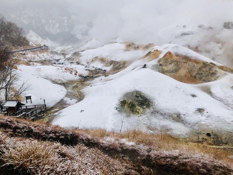 Traînée de marche en bois humide de sentier piéton de vallée d'enfer de Jigokudani avec l'énorme brume de soufre pendant pleuvoir image stock