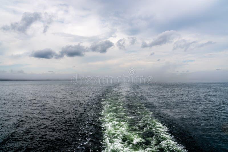 Traînée de sillage de bateau de croisière contre l'horizon flou avec des nuages photos libres de droits