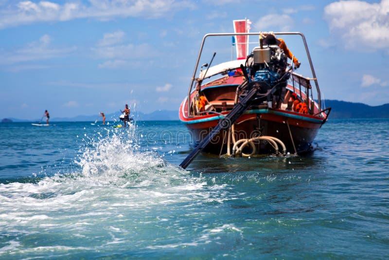Traînée et vagues sur la mer, éclaboussant du moteur de bateau Bateau de Longtail avec le conducteur au fond Jour ensoleillé  images libres de droits