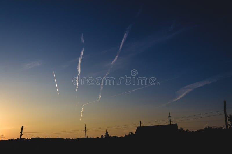 Traînées d'avion dans le ciel de coucher du soleil photos libres de droits