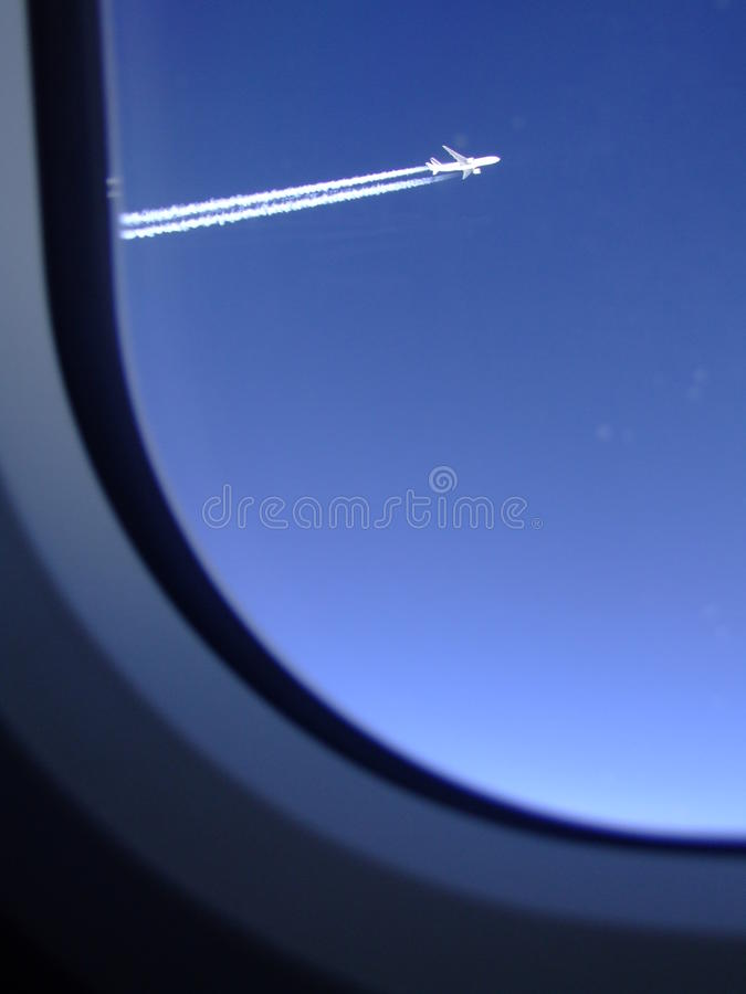 Traînées de jet d'une avion de ligne qui volait à côté de vu par la fenêtre de mon avion image libre de droits
