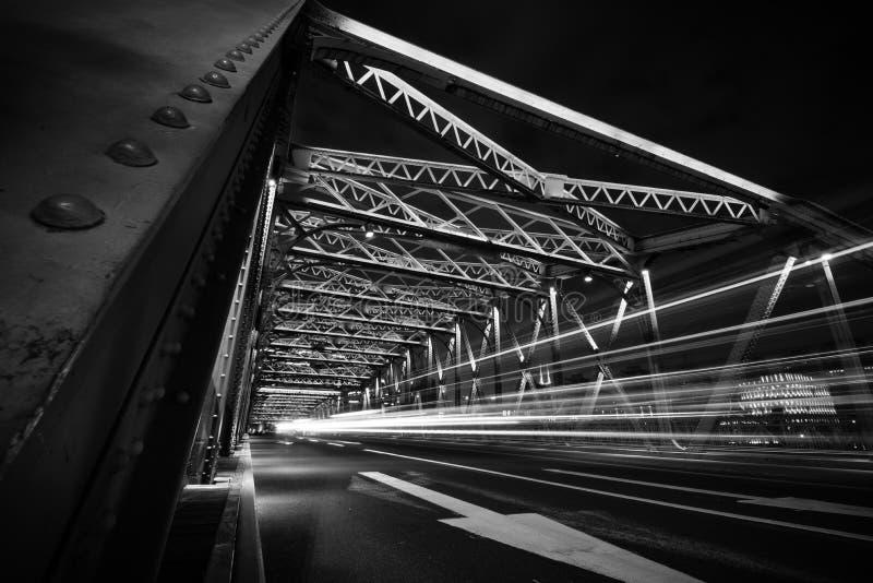 Traînées de lumière du trafic sur le pont en acier la nuit image stock