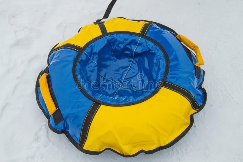 Traîneau rond en caoutchouc gonflable de tube de bébé pour le tour d'hiver avec des glissières, bleu-jaune, d'isolement sur le fo photos stock