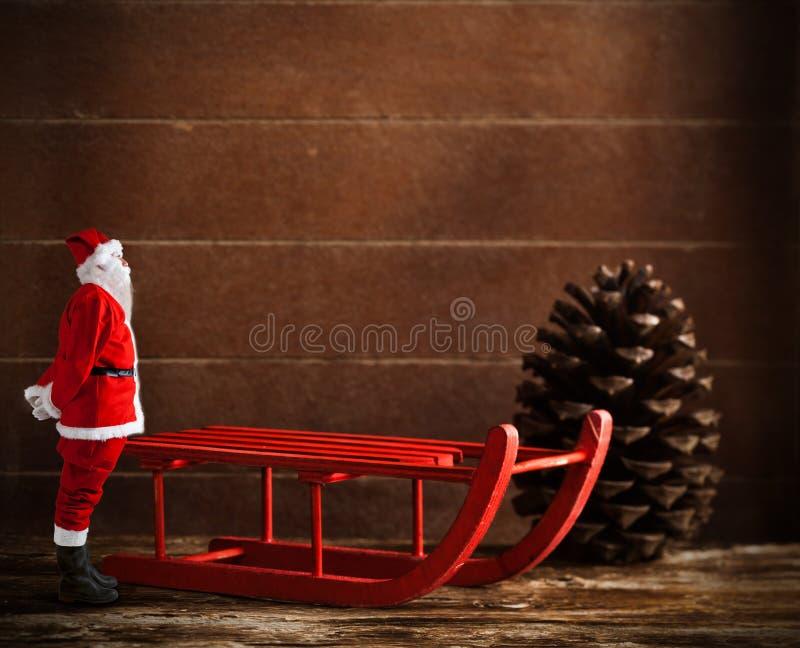 Traîneau rouge avec le cône et la Santa Claus de pin images stock