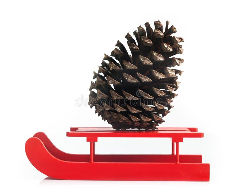Traîneau rouge en bois avec le cône de pin brun images libres de droits