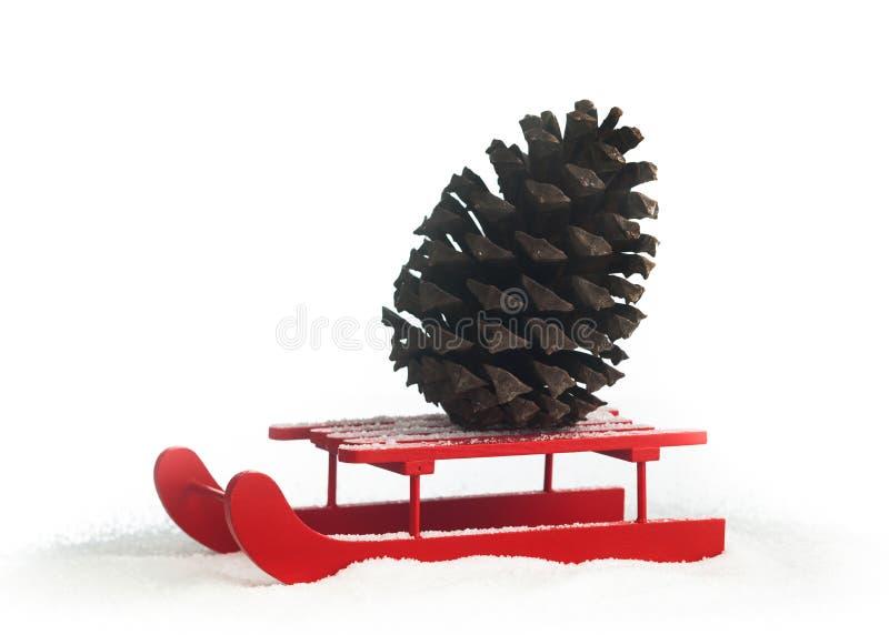 Traîneau rouge en bois avec le cône de pin brun photographie stock