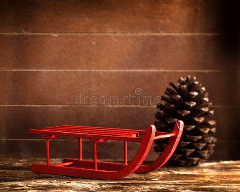 Traîneau rouge en bois avec le cône de pin brun photos stock