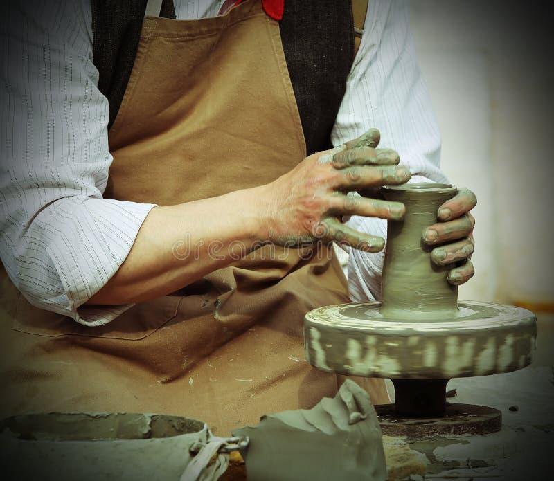 Traînez avec le tour de main pendant la production d'un pot avec de l'argile images libres de droits